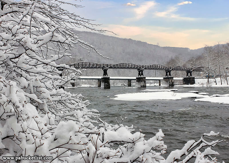 A snowy winter view of the Youghiogheny River along the Ferncliff Trail at Ohiopyle State Park
