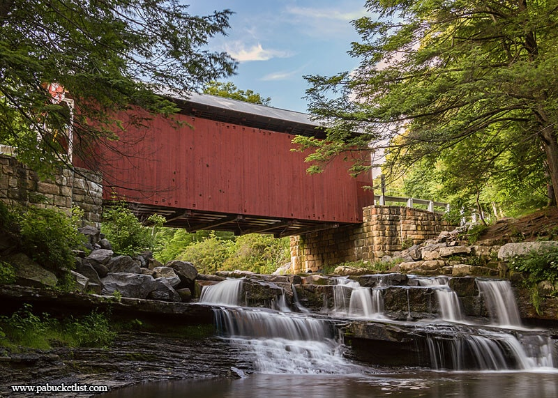 A late springtime view of the Pack Saddle Covered Bridge and the waterfalls on Brush Creek beneath it.