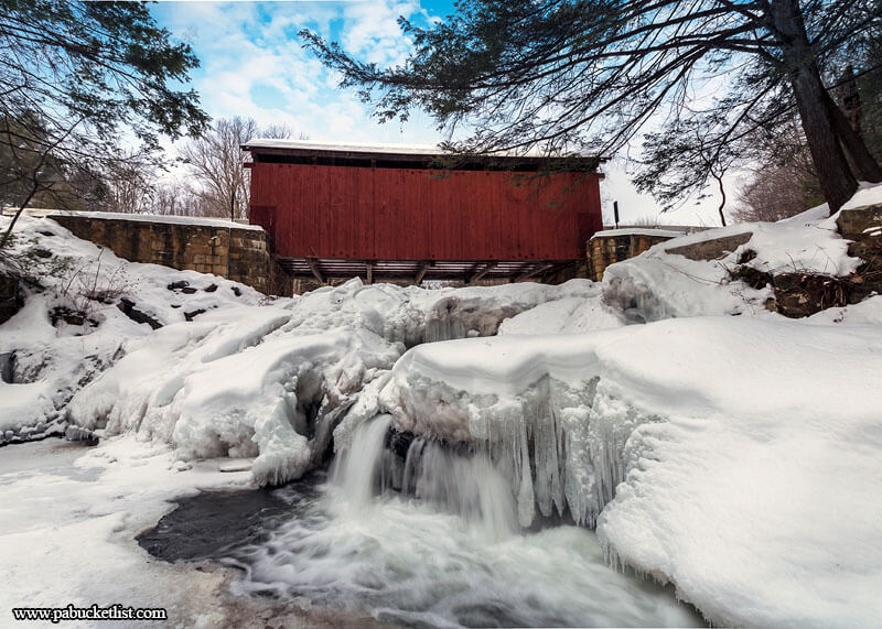 The partially frozen waterfalls on Brush Creek beneath the Pack Saddle Covered Bridge.