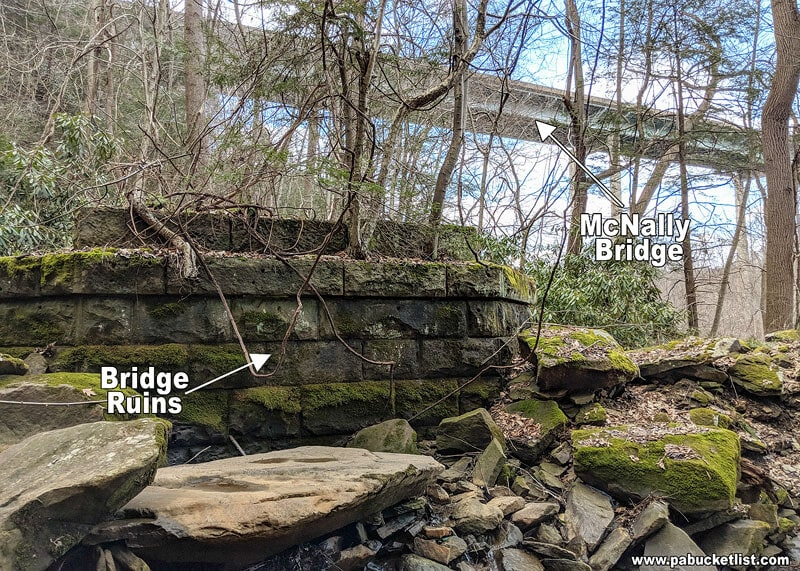 A view of the old bridge remnants along the Yoder Falls Trail, with the newer McNally Bridge in the background.