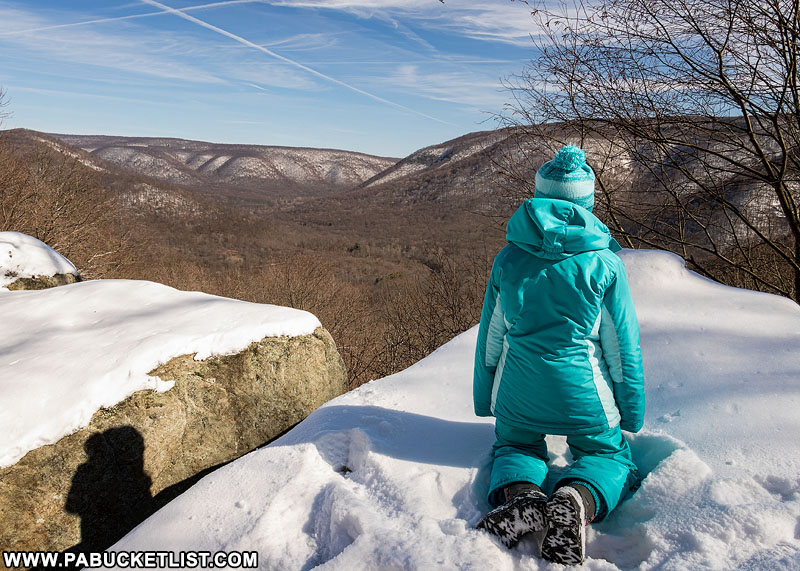 A young hiker takes in the winter view at Baughman Rock Overlook, Ohiopyle State Park.
