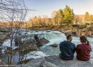 A young couple enjoying the magnificent view at the Ohiopyle Falls overlook along the Ferncliff Trail.