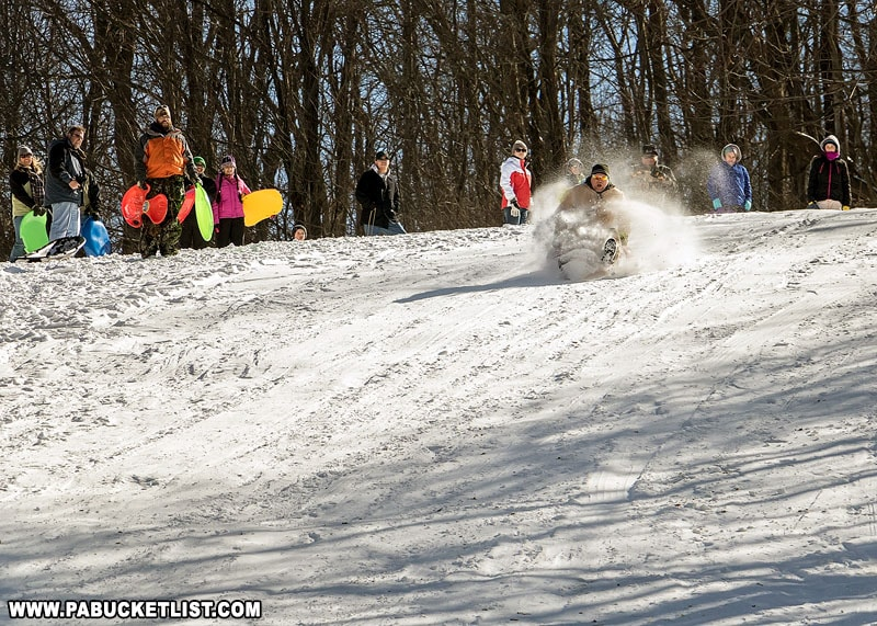 An adult sled rider tests his luck on the Sugarloaf sledding hill at Winterfest.