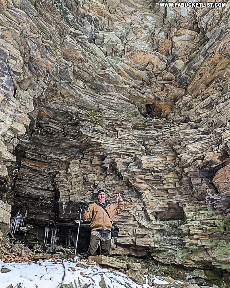 Steve Rubano standing in front of a missive rock formation near Abbott Run Falls.
