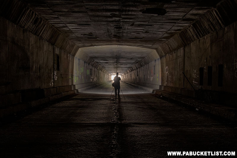 A photographer illuminated by a spotlight inside the Sideling Hill Tunnel.