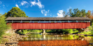A reflection of Kings Covered Bridge in the still waters of Laurel Hill Creek.