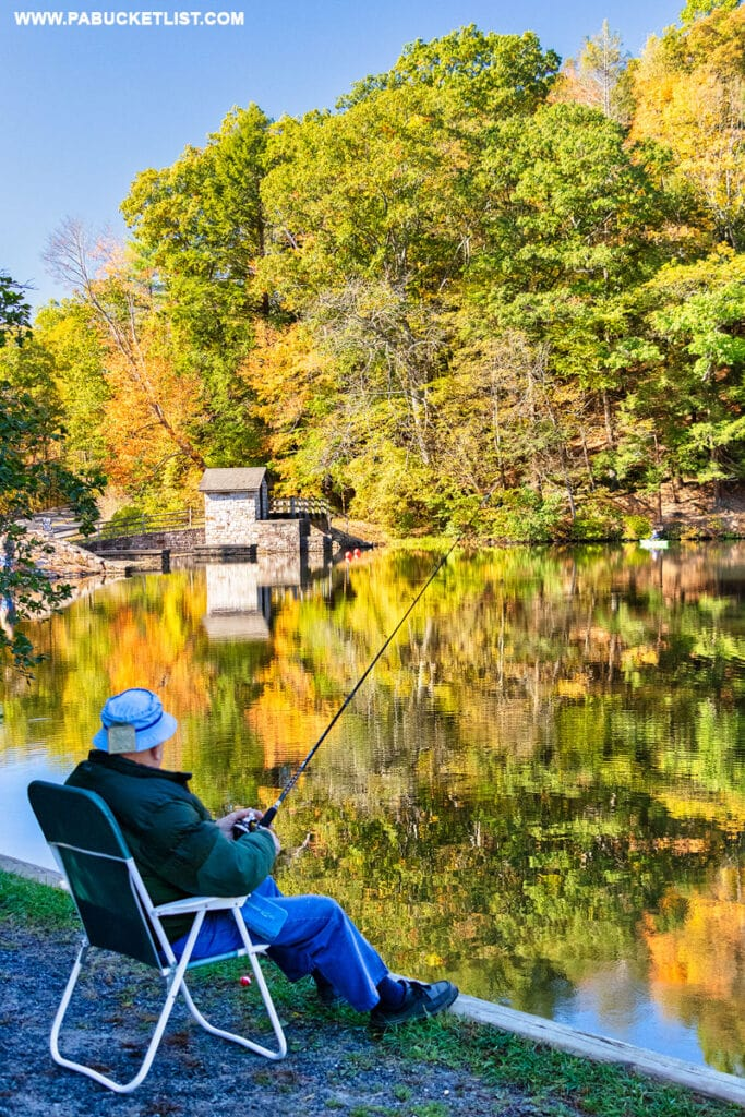 A fisherman surrounded by fall foliage at Greenwood Furnace State Park in Huntingdon County.