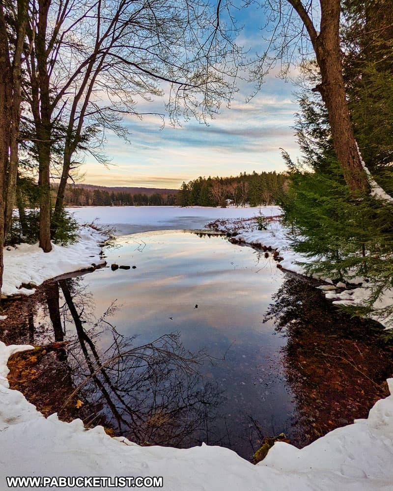 Winter sunset reflected on the surface of Black Moshannon Lake.