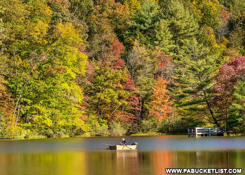 A boater on Greenwood Lake at the height of fall foliage season.