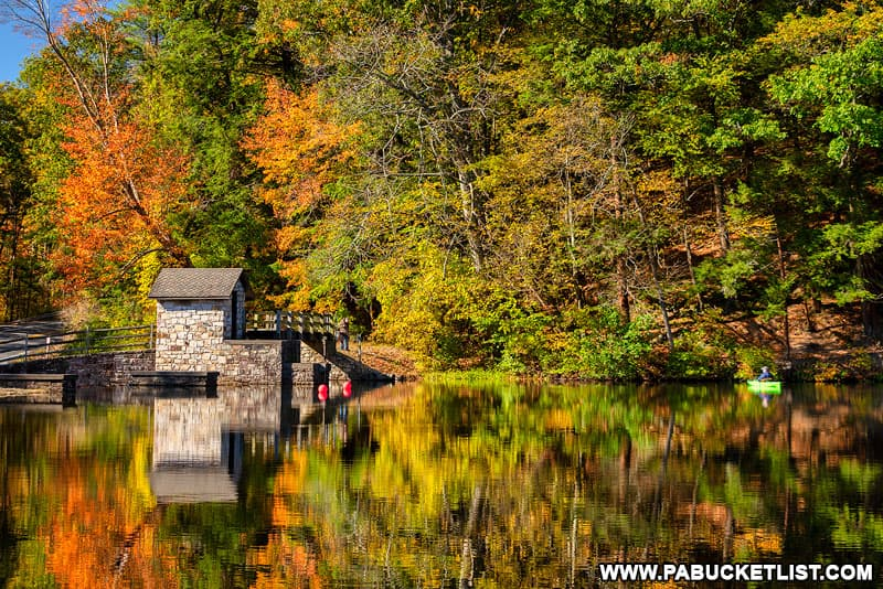 A kayaker on the lake at Greenwood Furnace State Park during the peak of fall foliage season.