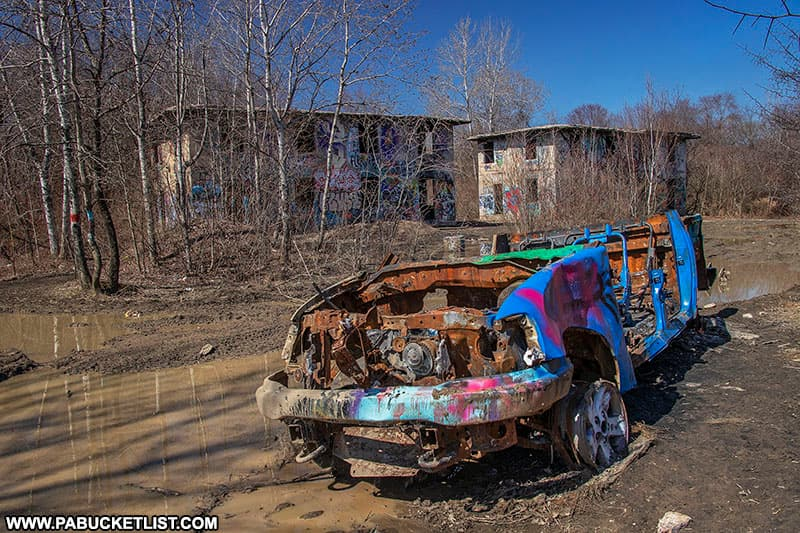 A burned-out truck resting on a road in Concrete City.