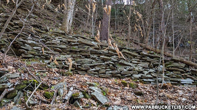 Stacked stone retaining wall along the old railroad grade next to Benjamin Hollow Falls.
