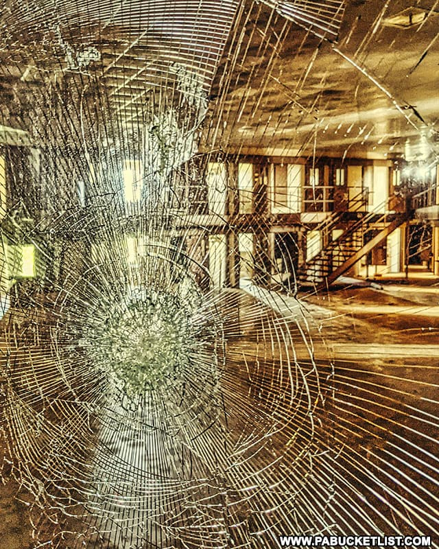 Looking at a cell block through shattered glass at the abandoned Cresson State Prison.