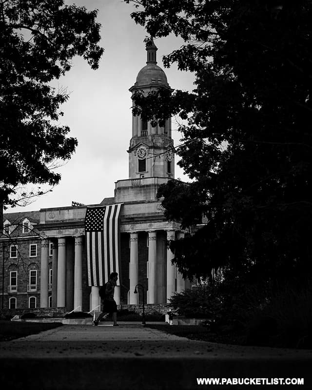 A student passes in front of the large American flag draped in front of Old Main at Penn State