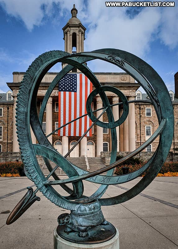 Old Main and Old Glory in the background, the armillary sphere (gift of the class of 1966) in the foreground.