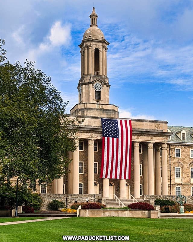 The Stars and Stripes hanging from the pillars of Old Main at Penn State.